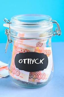 Banco con dinero ruso. texto en ruso: vacaciones.