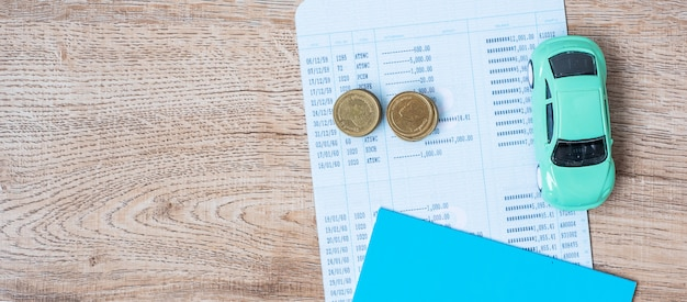 Banco del libro con el coche en la mesa de madera. financiero, dinero, refinanciamiento, automóvil por efectivo y concepto de seguro de automóvil