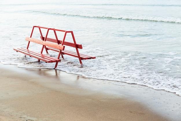 Banco rojo cerca del agua de mar