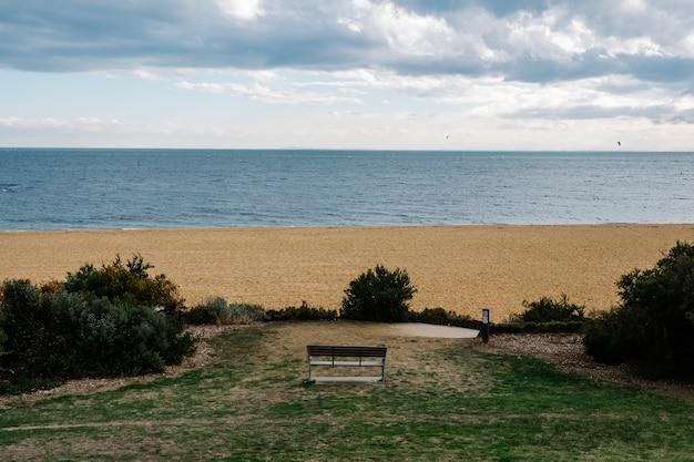 Banco solitario en parque y mar y arena.