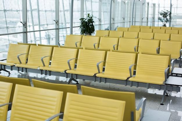 Banco en la terminal del aeropuerto. área de espera de la terminal del aeropuerto vacía con sillas.