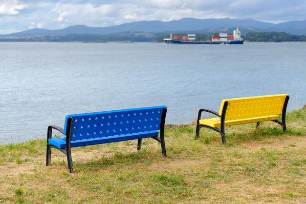 Bancos azules y amarillos en la orilla con un carguero en el horizonte