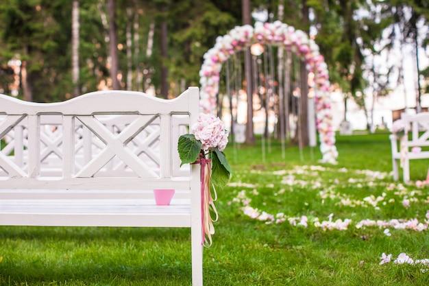 Bancos de boda y arco de flores para ceremonia al aire libre.