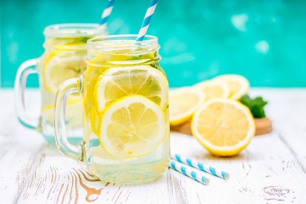 Bancos con las manijas con limonada fría en un fondo de madera blanco. limones