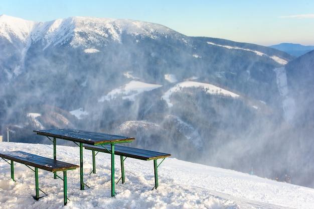 Bancos y la mesa en la cima de una montaña con una hermosa vista sobre una escena de invierno con montañas, árboles y nieve.