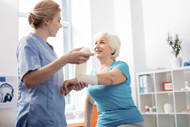 Banda elastica. enfermera encantada agradable mirando a su paciente mientras sostiene un vendaje blanco