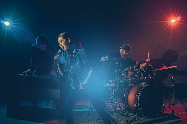 Banda de músico mano sosteniendo el micrófono y cantando una canción y tocando un instrumento de música con fello