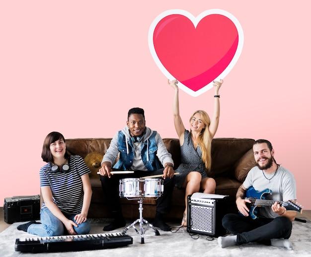 Banda de músicos sosteniendo un emoticono de corazón.