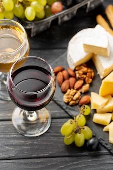 Bandeja de ángulo alto con queso y variedad de vino tinto.