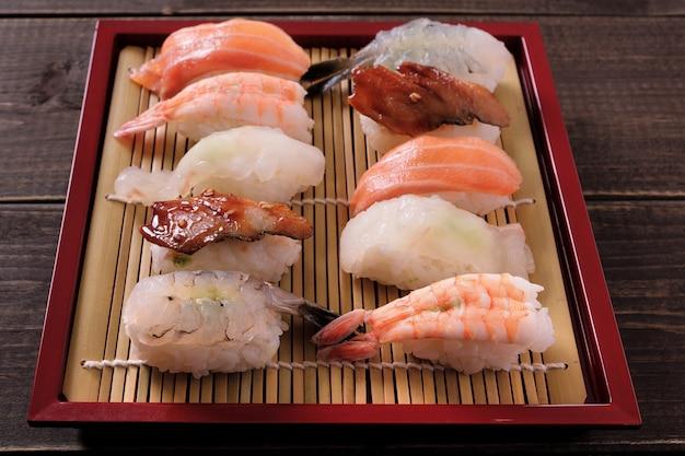 Bandeja de bambú rojo surtido de sushi.
