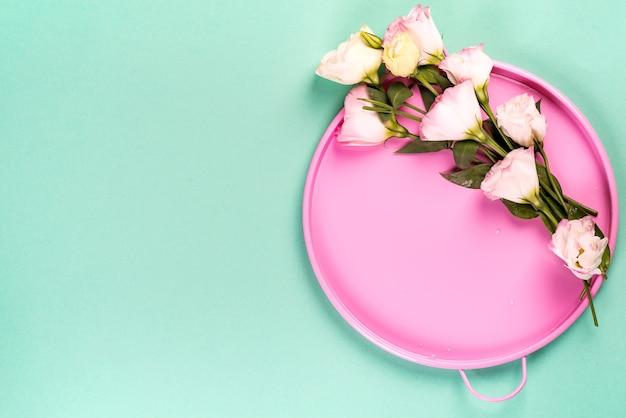 Bandeja de círculo de estaño rosa con ramo de eustoma en superficie azul, vista superior con espacio de copia para su diseño, marco. composición de bodegones.