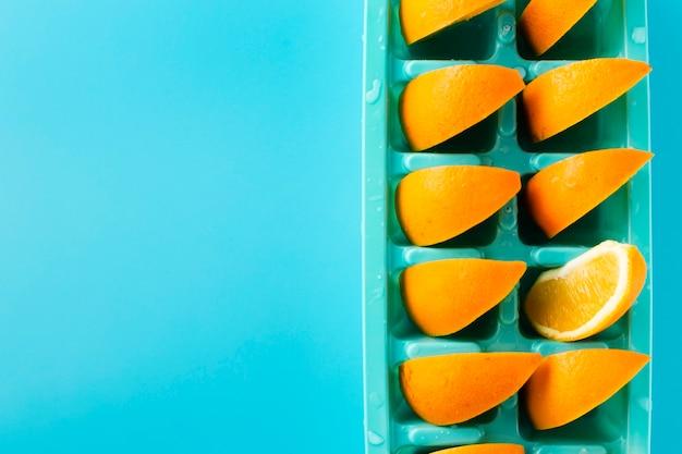 Bandeja de cubitos de hielo con rodajas de naranja.