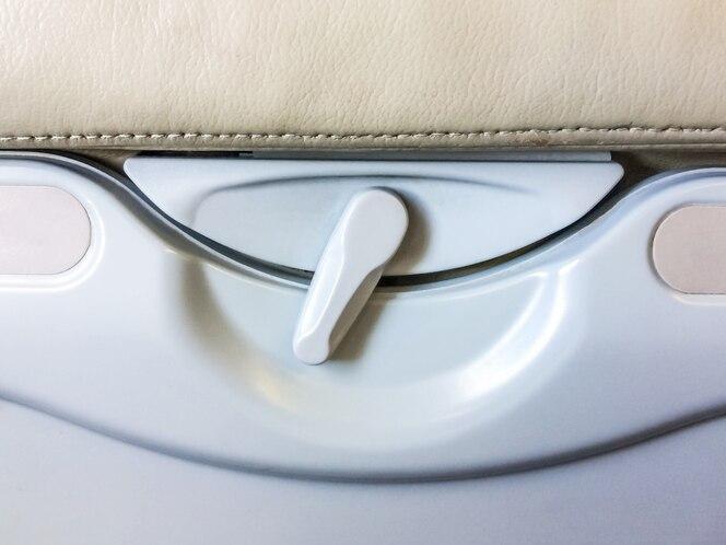 Bandeja de comida y asiento de pasajero trasero de estante para bebidas en el avión.