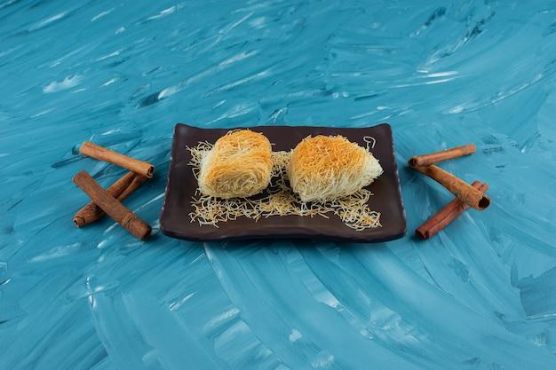 Una bandeja de delicias turcas con canela en rama sobre un fondo azul.