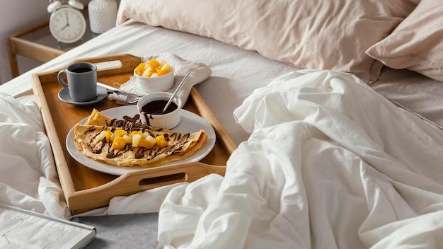 Bandeja de desayuno de ángulo alto en la cama