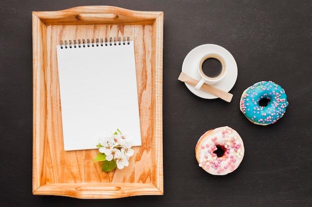 Bandeja con desayuno y cuaderno sobre mesa