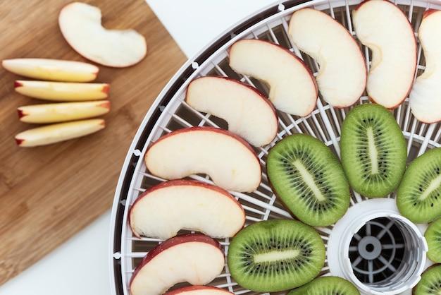 Bandeja deshidratadora con rodajas de kiwi y manzanas. detrás hay una tabla de cortar con rodajas de manzana. vista superior.