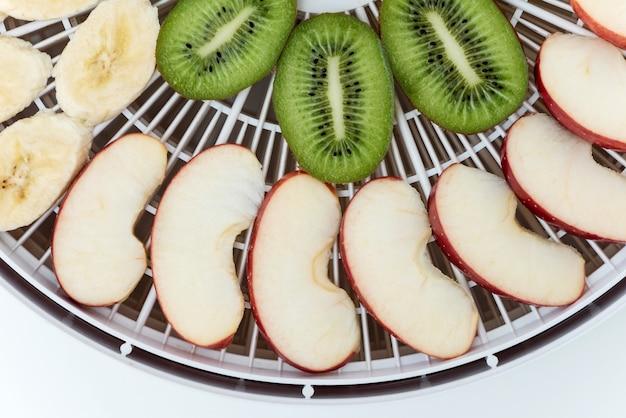 Bandeja deshidratadora con rodajas de kiwi y manzanas. vista superior.