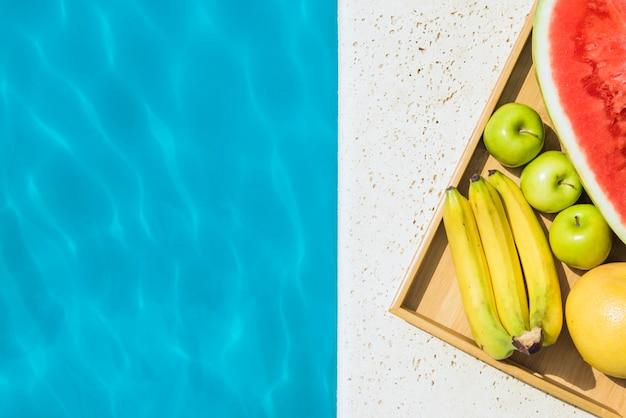 Bandeja con frutas colocadas en el borde de la piscina.