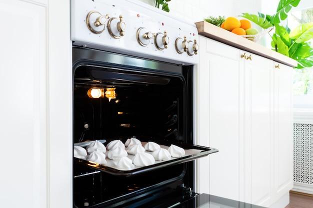 Bandeja de la hornada con los merengues dulces en el horno en cocina.