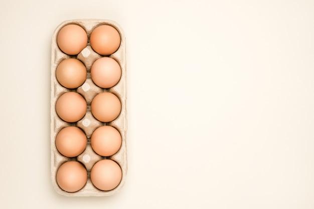Una bandeja de huevos de gallina fresca marrón sobre fondo beige.