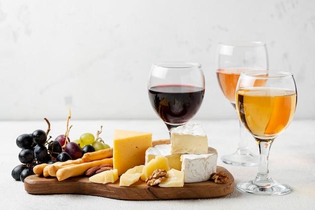 Bandeja de madera de alto ángulo con queso y vino para degustación.