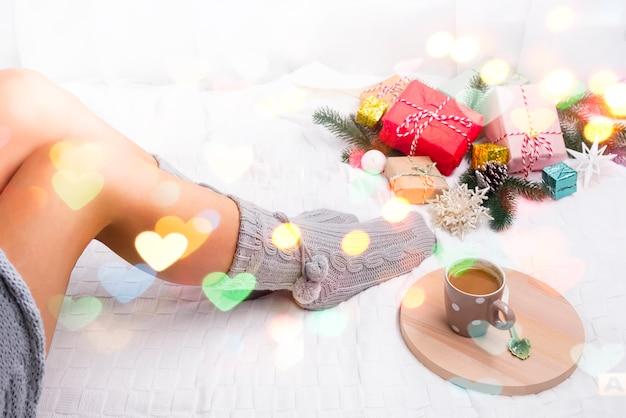 Bandeja de madera con café en la cama y pies femeninos en calcetines de punto con regalos