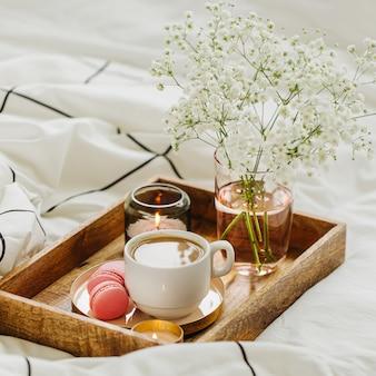 Bandeja de madera con café y velas con flores en la cama. desayuno en la cama. concepto hygge.