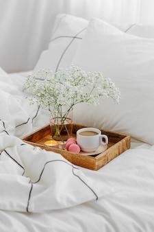 Bandeja de madera con café y velas con flores en la cama. sábanas blancas con manta a rayas y almohada. desayuno en la cama. concepto hygge.