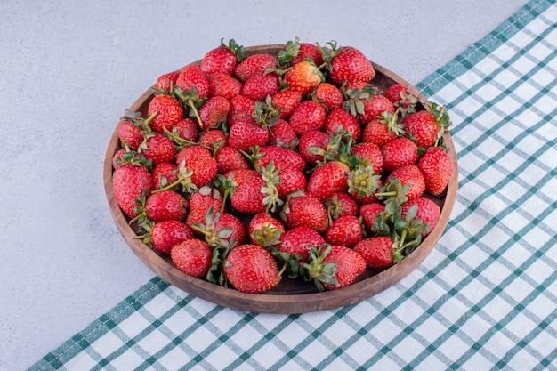 Bandeja de madera llena de fresas sobre fondo de mármol. foto de alta calidad