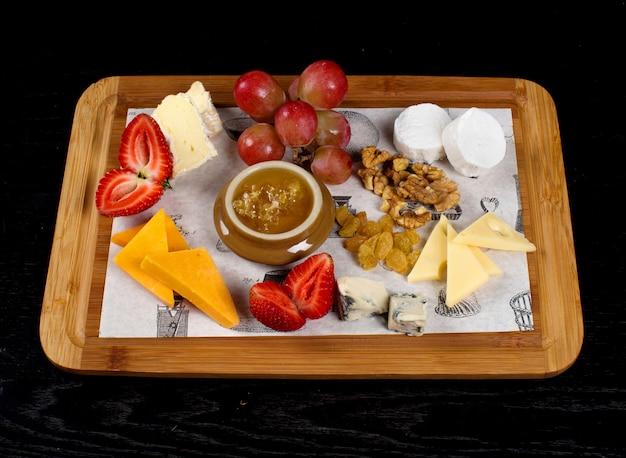 Bandeja de madera con quesos, frutas y un tarro de miel.