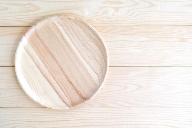 Bandeja de madera redonda vacía sobre fondo de mesa de madera