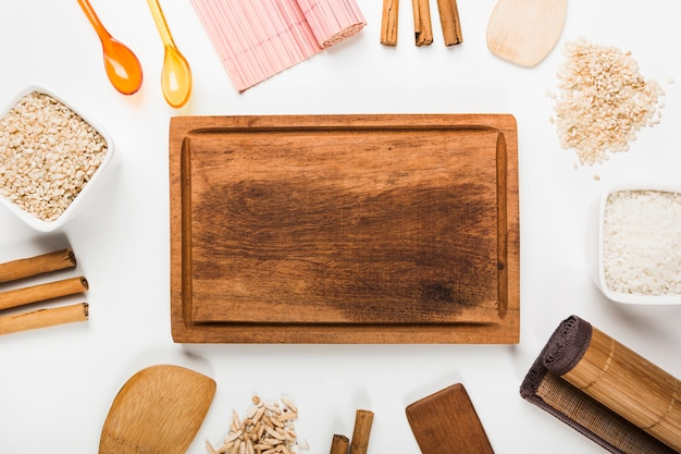 Bandeja de madera rodeada de arroz crudo; palitos de canela; espátula sobre fondo blanco