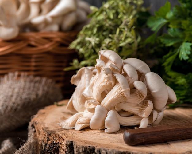 Bandeja de madera con setas ostra crudas sobre mesa de madera