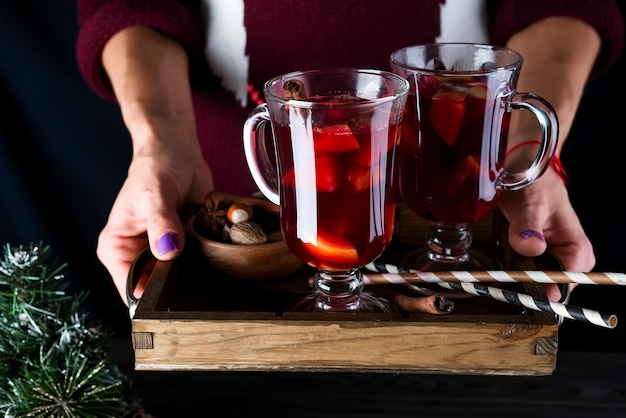 Bandeja de madera con vino caliente casero caliente con frutas y especias en manos femeninas en un oscuro