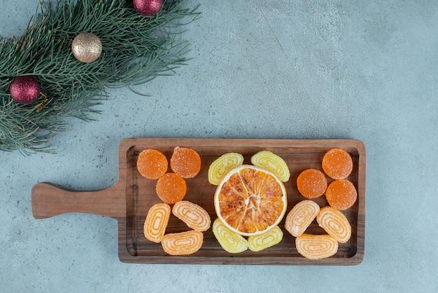 Bandeja de mermeladas y una rodaja de naranja seca junto a una hilera de guirnaldas sobre mármol.