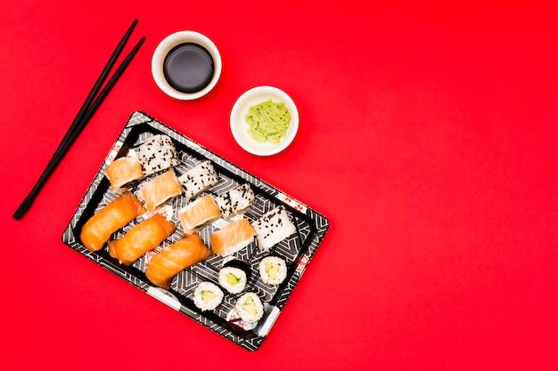 Bandeja negra rellena de rollos cerca de wasabi y salsa de soya en mostrador rojo