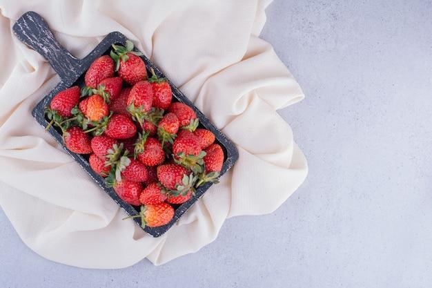 Bandeja negra sobre tela blanca con un montón de fresas sobre fondo de mármol. foto de alta calidad