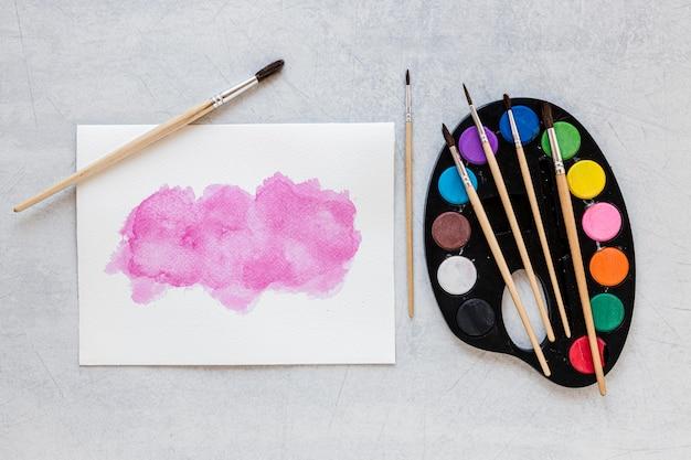 Bandeja de paleta de colores y rosa sobre papel