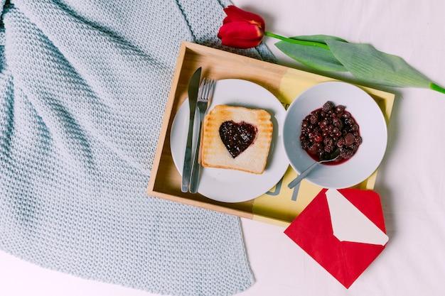 Bandeja con pan tostado con mermelada en forma de corazón y bayas.