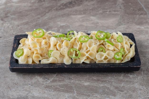 Una bandeja de pasta farfalle italiana de pepperoni, sobre el mármol.