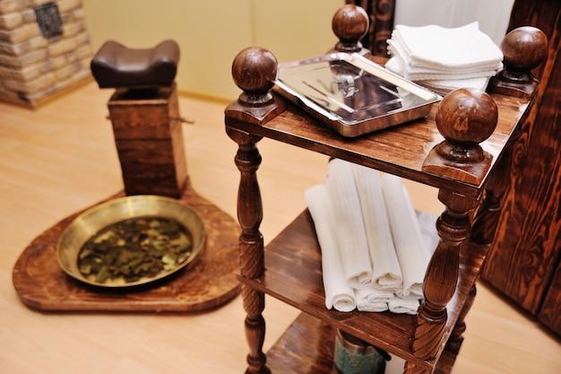 Una bandeja de pedicura con hojas de roble en un salón de spa