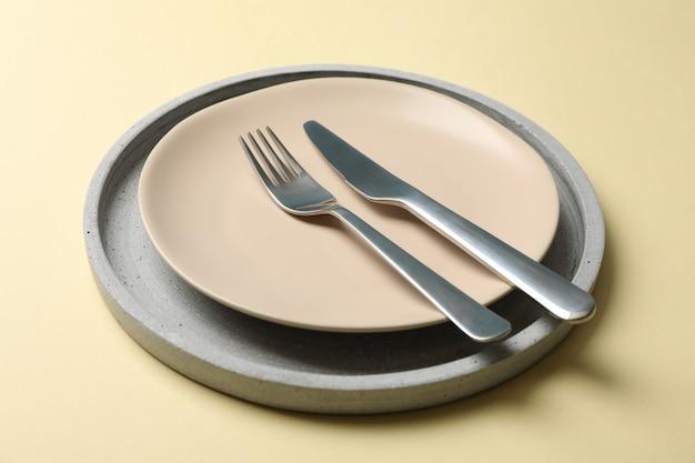Bandeja con plato, tenedor y cuchillo en color beige.