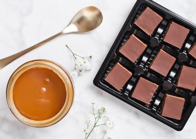 Bandeja de postres sobre pastelitos de caramelo y bizcocho sobre tabla de mármol con tarro de caramelo salado y cuchara dorada