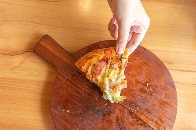 La bandeja de salsa de pizza caliente con ingredientes para pizza incluye jamón, cerdo, pimentón y verduras, pizza,