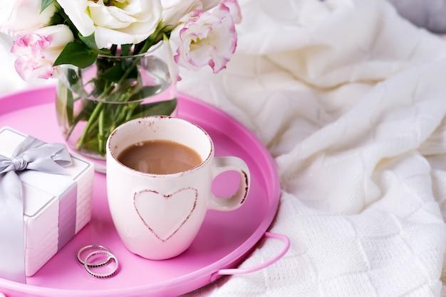 Una bandeja con una taza de café, caja de regalo, flores y anillos en la cama. oferta de bodas de san valentín