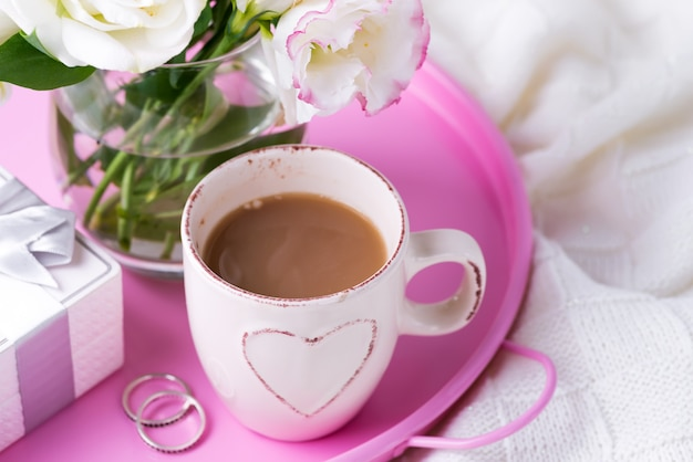 Una bandeja con una taza de café, caja de regalo, flores y anillos en la cama.