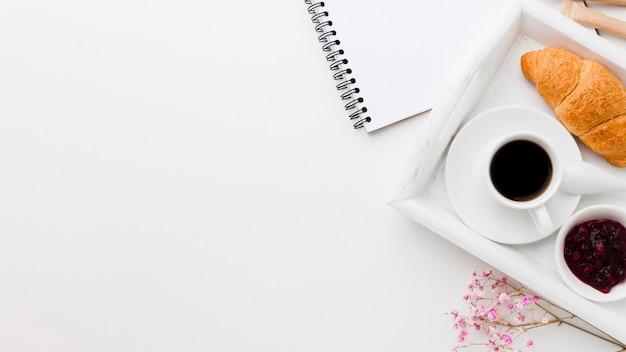 Bandeja con taza de café y croissant al lado del cuaderno