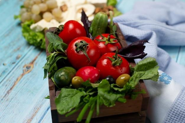 Bandeja de verduras con tomate, pepino y hierbas.