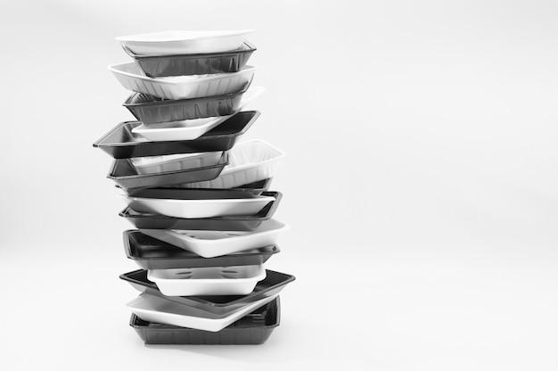 Bandejas de contenedores de alimentos de espuma blanca y negra bandejas de espuma de poliestireno apiladas aisladas sobre fondo blanco